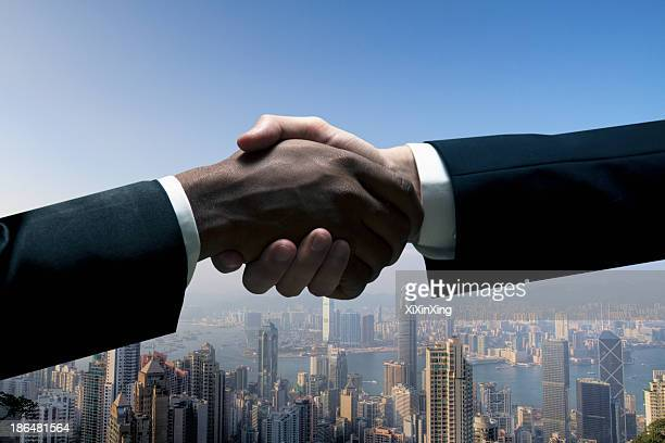 close up of businessmen shaking hands with cityscape in the background - cuff sleeve stock pictures, royalty-free photos & images