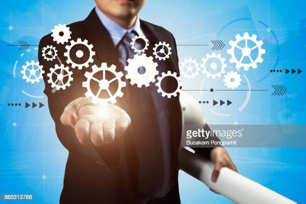 Close up of businesswoman and engineer holding gears in hand. technology concept with light blue color background