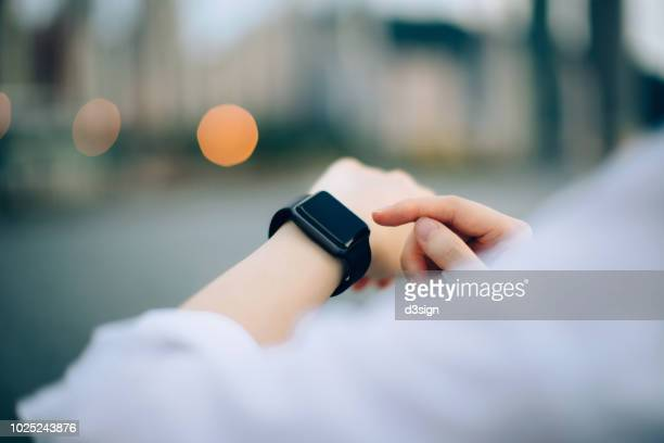 close up of businesswoman checking her smartwatch in downtown city - 知能 ストックフォトと画像