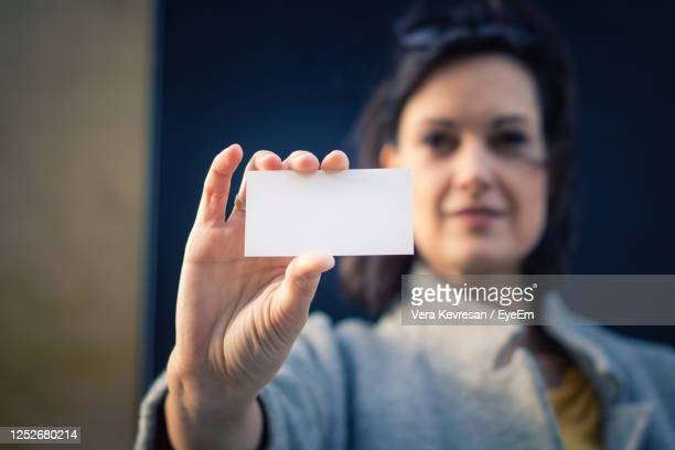 close up of businesswoman holding blank business card. woman showing an empty id card. - id card template stock pictures, royalty-free photos & images
