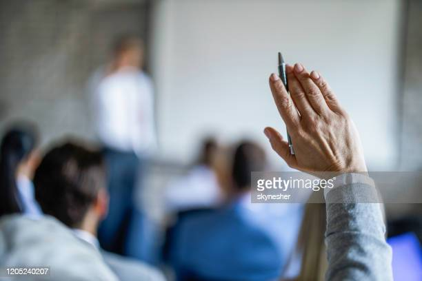 close up of businesswoman raising her hand on a seminar in board room. - domanda e risposta foto e immagini stock