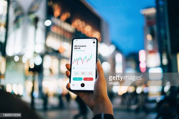 close up of businesswoman reading financial stock market analysis on smartphone on the go, in downtown city street against illuminated urban skyscrapers in the evening. business on the go - cryptocurrency stock pictures, royalty-free photos & images