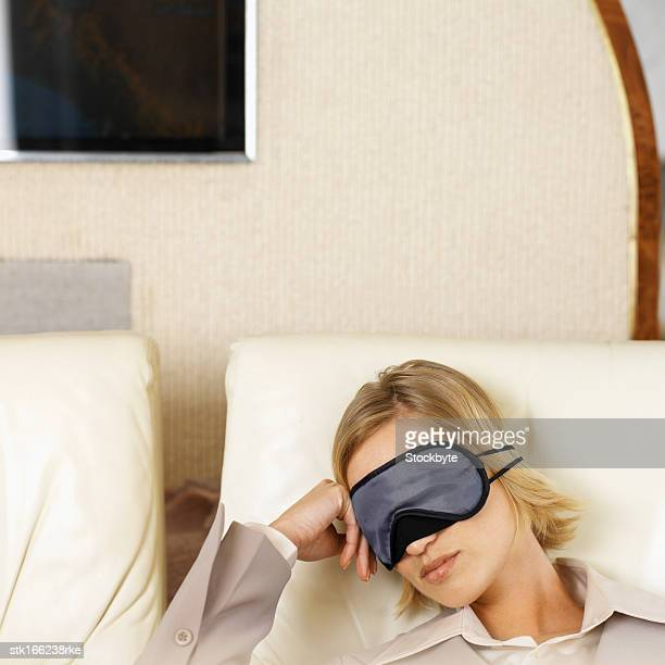 close up of businesswoman sleeping wearing eye mask