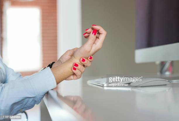 close up of businesswoman with wrist pain - tendon stock photos and pictures