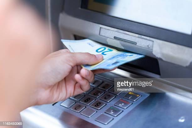 close up of businesswoman withdraw money on a cash machine - geldautomat stock-fotos und bilder