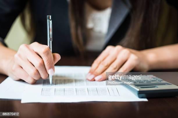 Nahaufnahme der Businesswomans Hände mit Stift einige finanzielle Berechnungen. Flachen DOF, Fokus auf Stift