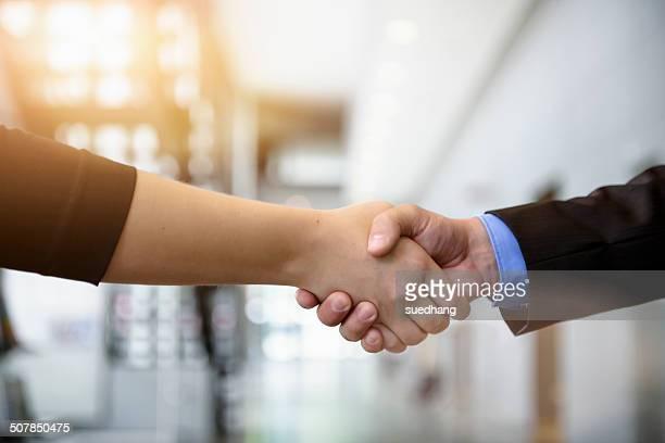 close up of businesswomen and businessman shaking hands in office - handschlag stock-fotos und bilder