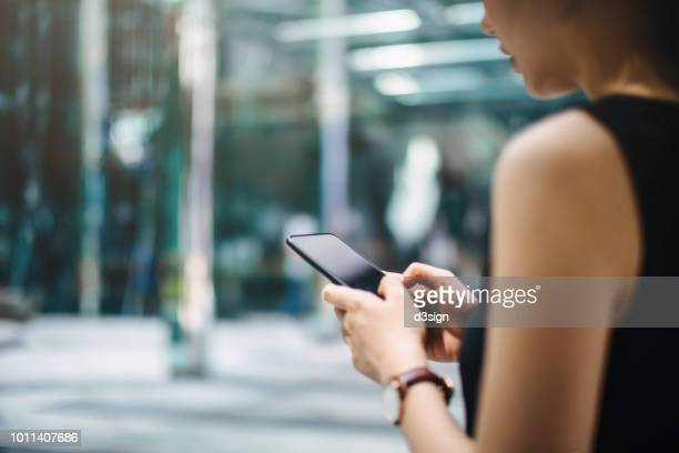 close up of busy businesswoman emailing on mobile phone by office towers in downtown financial district - online banking stock pictures, royalty-free photos & images
