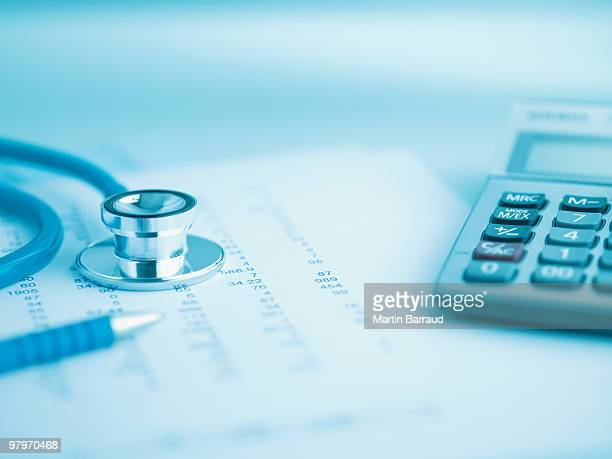 Close up of calculator, data and stethoscope