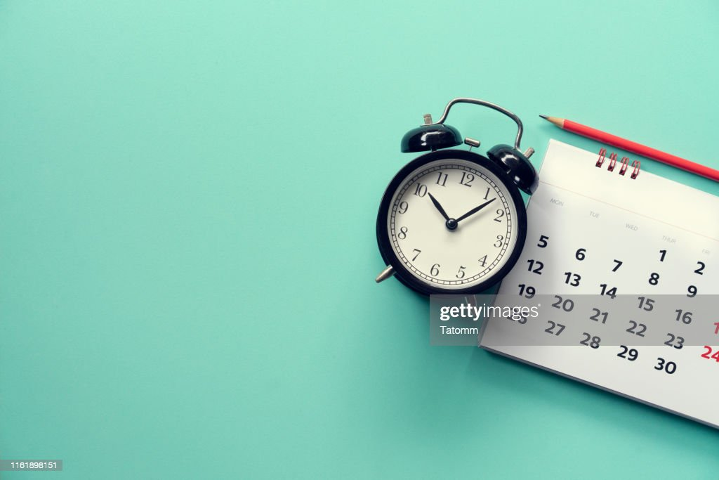 close up of calendar and alarm clock on the green background, planning for business meeting or travel planning concept : Stock Photo