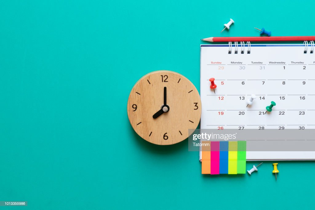 close up of calendar and clock on green background, planning for business meeting or travel planning concept : Stock Photo