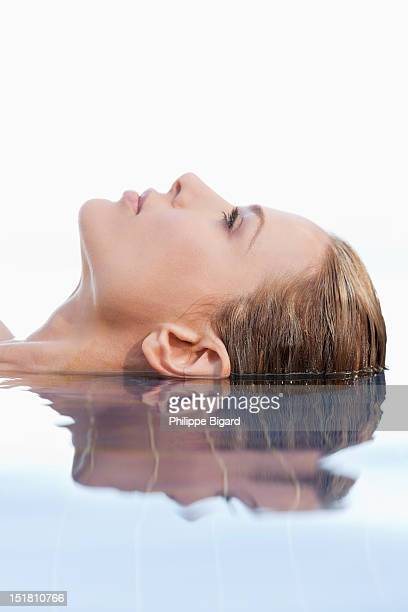 Close up of calm woman laying in infinity pool