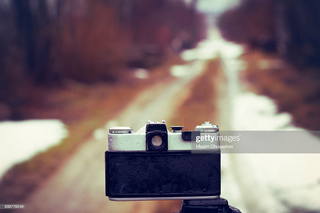 Close up of camera on tripod on snowy road : Foto stock