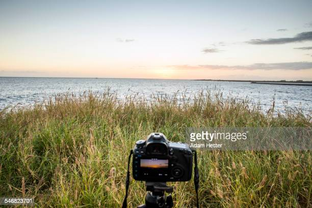 Close up of camera photographing sunset over ocean horizon
