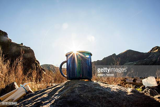 Close up of camping mug under remote mountains