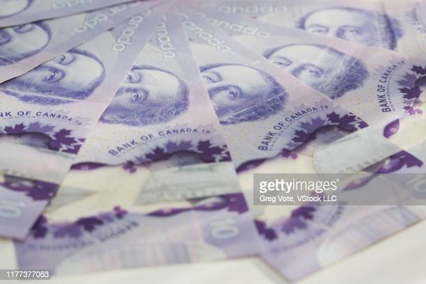 close up of canadian ten dollar bills - canadian currency stock pictures, royalty-free photos & images