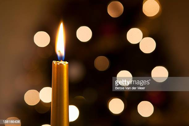 Close up of candle in front of Christmas tree