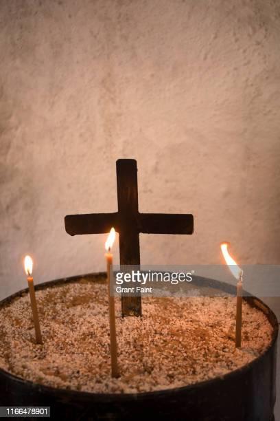 close up of candles in church. - crucifijo fotografías e imágenes de stock