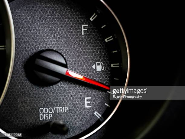 close up of car fuel gauge with red needle - gas tank stock photos and pictures