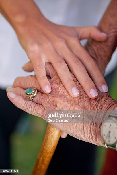 Close up of care assistants hand reassuring senior woman
