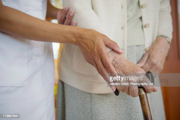 Close up of caretaker helping older woman walk