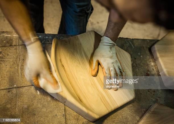 nahaufnahme des zimmermanns, der ein holz mit sandpapier restauriert. - designer einrichtung stock-fotos und bilder