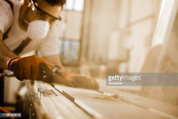 close up of carpenter using air pump to blow sawdust from a plank. - lumber industry stock pictures, royalty-free photos & images