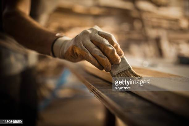 close up of carpenter using brush while applying protective varnish to a piece of wood. - furniture stock pictures, royalty-free photos & images