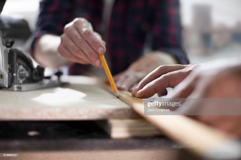 Close up of carpenters marking measurements in furniture making workshop : Stock Photo