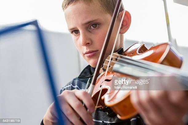 Close up of Caucasian boy playing violin