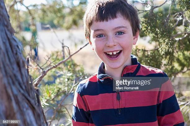 Close up of Caucasian boy smiling near tree