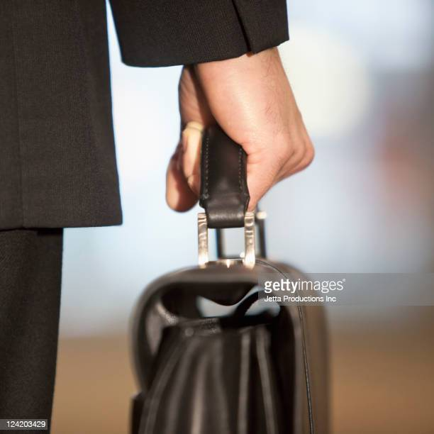 Close up of Caucasian businessman carrying briefcase