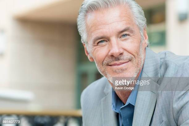 close up of caucasian businessman smiling - endast medelålders män bildbanksfoton och bilder