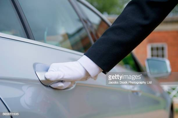Close up of Caucasian butler opening car door