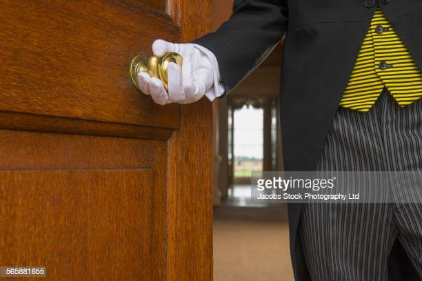 Close up of Caucasian butler opening door