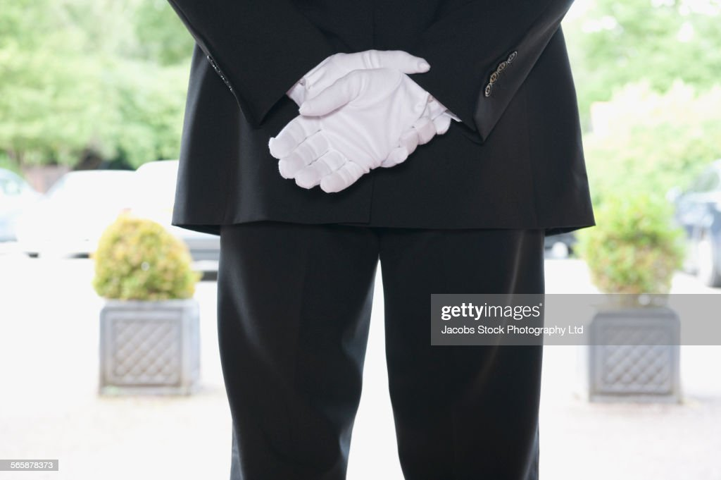 Close up of Caucasian butler waiting at hotel entrance : Stock Photo