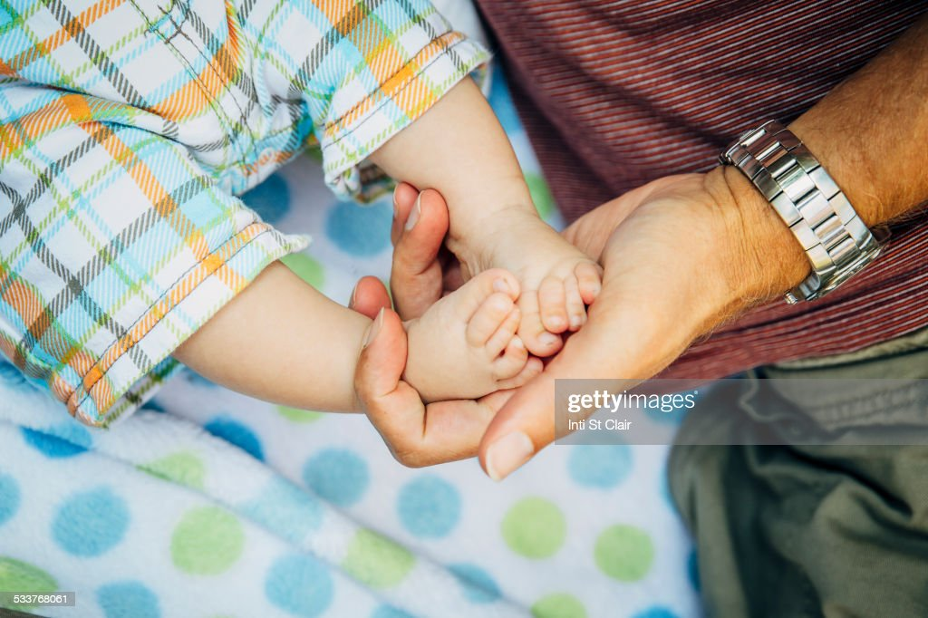 Close up of Caucasian father holding feet of baby boy : Foto stock