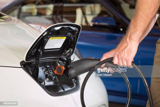 Close up of Caucasian man recharging electric car