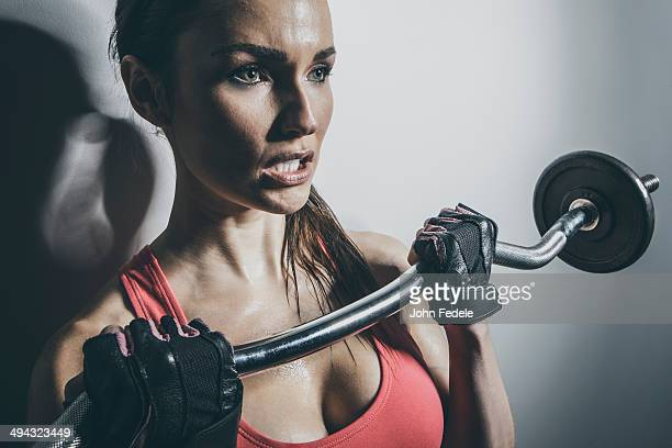 close up of caucasian woman lifting barbell - clenching teeth stock pictures, royalty-free photos & images