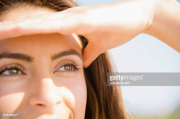 Close up of Caucasian woman shielding eyes from sun