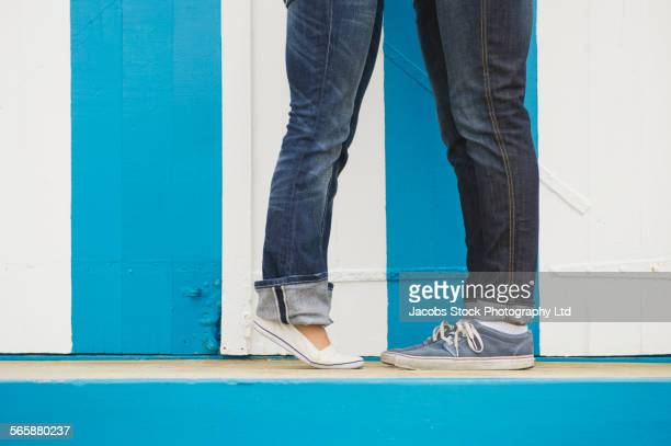 Close up of Caucasian woman standing on tiptoes to kiss boyfriend