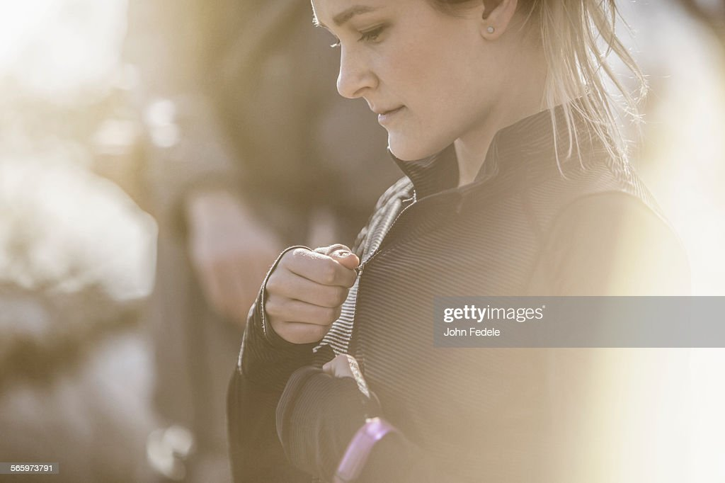 Close up of Caucasian woman zipping jacket : Stock Photo