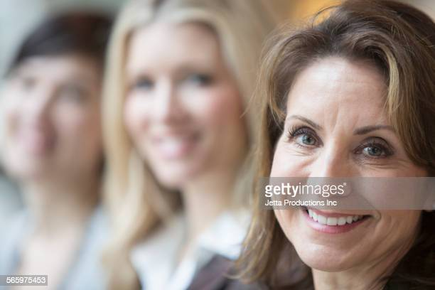 Close up of Caucasian women smiling in a row
