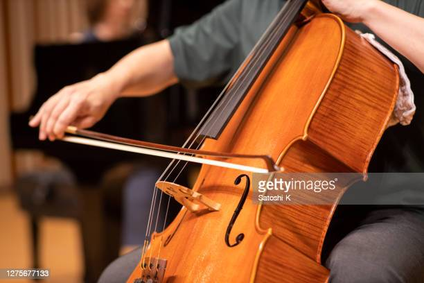 close up of cellist playing at classical concert - classical musician stock pictures, royalty-free photos & images