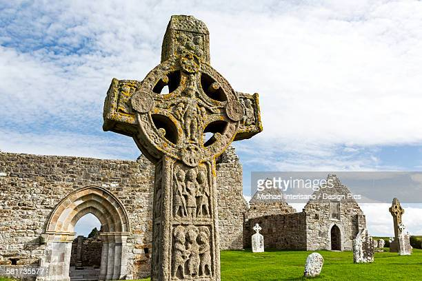 Close up of celtic cross and stone roofless churches in background