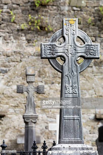 Close up of celtic cross in cemetery with stone wall in background