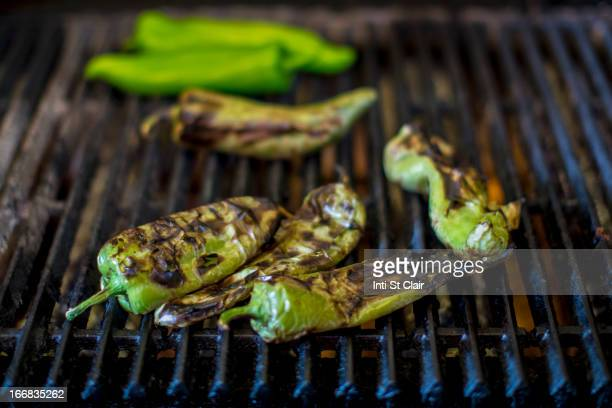 close up of charred chilies on grill - jalapeno stock-fotos und bilder
