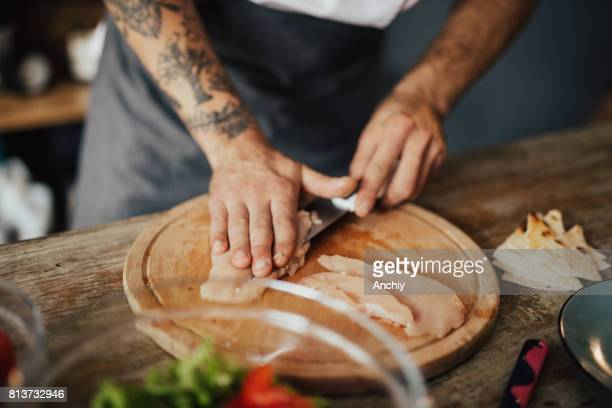 Close up of chef's hands cutting chicken meat on the wooden board