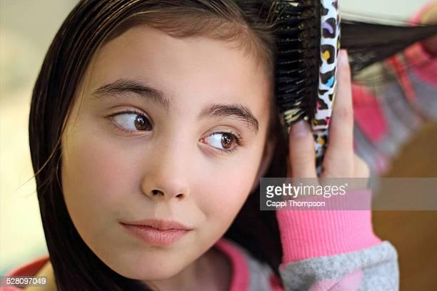 Close up of child brushing hair