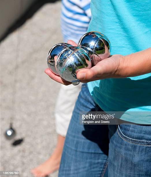 Close up of child holding silver balls